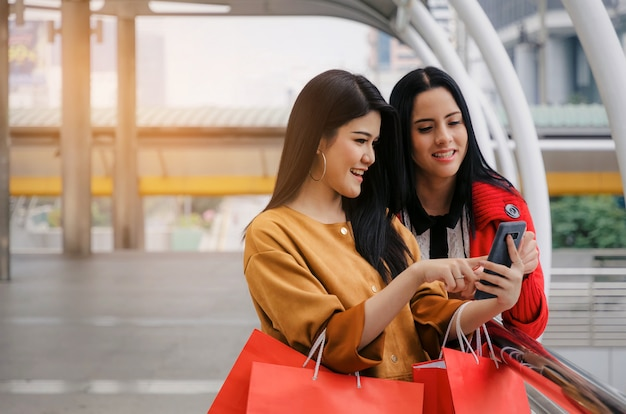 Happy beautiful smiling asian and caucasian young woman with mobile phone and holding shopping bags Premium Photo