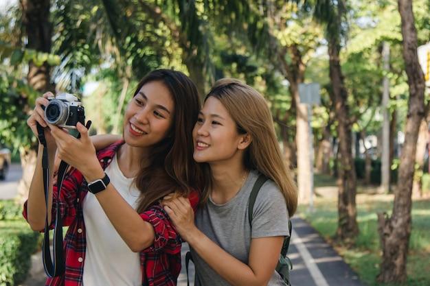 Happy beautiful traveler asian friend women carry backpack Free Photo