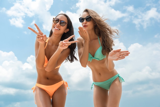 Happy beautiful woman friends in colorful bikinis at the beach in summer Premium Photo