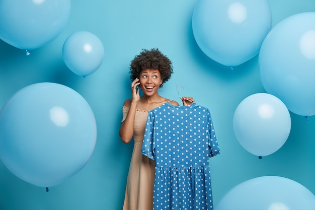Happy beautiful woman holds blue polka dot dress on hanger, calls someone and uses her phone, prepares for special event, chooses outfit, poses around balloons. clothing, wardrobe, fashion concept Free Photo