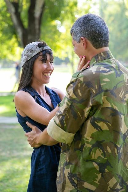 軍から戻ってくる夫を見ている幸せな美しい女性。兵士のカップを着て、屋外に立って、笑顔で制服を着た彼氏と抱きしめる陽気な女性。軍事と愛の概念 無料写真