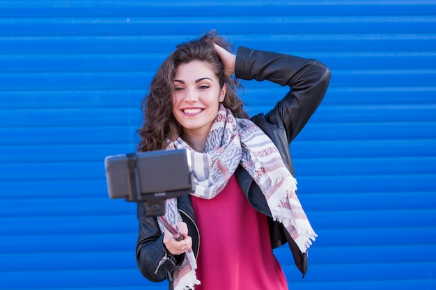 Happy beautiful woman taking a selfie with smart phone over blue background. Premium Photo