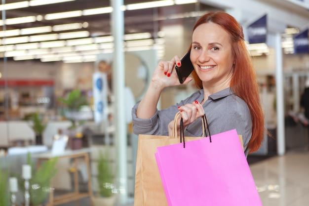 モールで買い物をしながら電話で話している幸せな美しい女性は、スペースをコピーします。消費者、販売コンセプト Premium写真