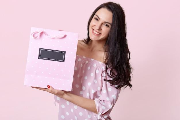 水玉のドレスに身を包んだ黒い髪の幸せな美しい女性は、プレゼントバッグを保持している、肯定的な表情 無料写真