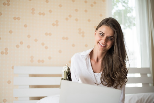 Happy beautiful woman working on a laptop on the bed in the house Free Photo