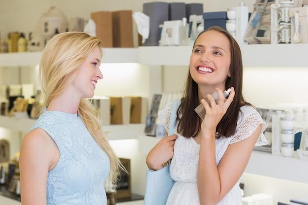 Happy beautiful women spraying perfume Premium Photo