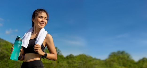 Happy beautiful young asian woman with her white towel over her neck, standing smiling and holding her water bottle to drink after her morning exercise at an outdoor park Premium Photo