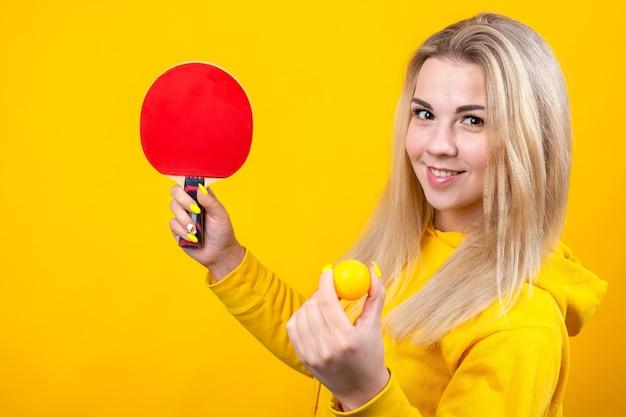 캐주얼 노란색 스포티 한 옷에 행복 한 아름 다운 젊은 금발의 여자는 공과 라켓을 들고 탁구를 재생합니다. 프리미엄 사진