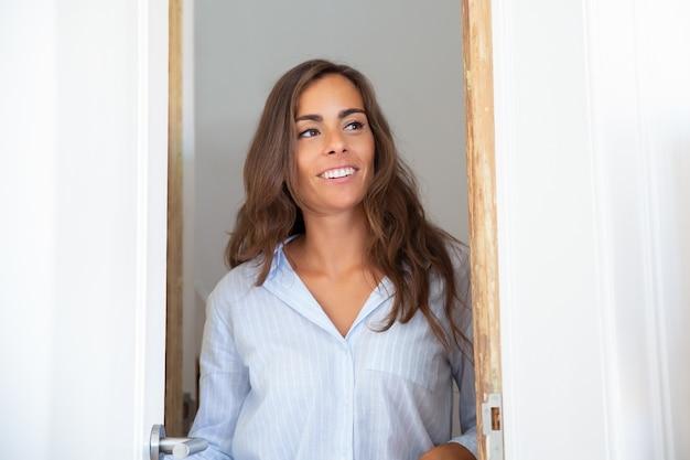 행복 한 아름 다운 젊은 히스패닉 여자 문을 열고, 출입구에 서, 아파트 내부를 찾고 웃 고 무료 사진
