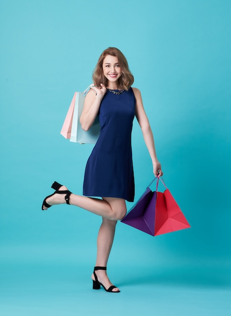Happy beautiful young woman in blue dress and hand holding shopping bag Premium Photo