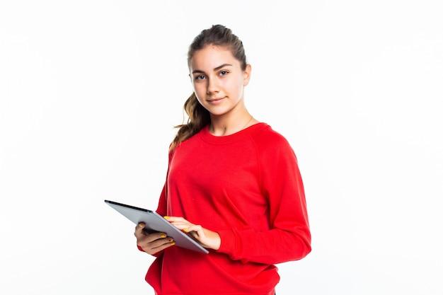 Ragazza teenager di bellezza felice che manda un sms su una compressa su una parete bianca Foto Gratuite