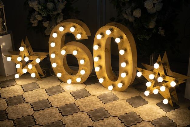 С днем рожденья! дневное украшение интерьера на шестьдесят лет. звездные огни. числа 60 вырезаны из дерева с подсветкой. Premium Фотографии
