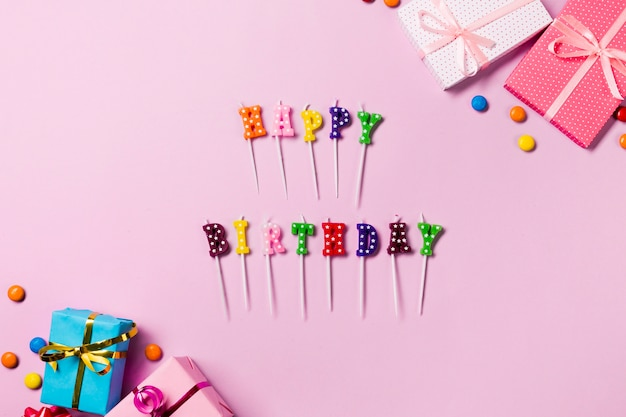 Happy birthday candle sticks with gift boxes and gems on pink backdrop Free Photo