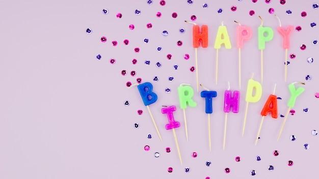 Candele e coriandoli di buon compleanno su sfondo viola Foto Gratuite