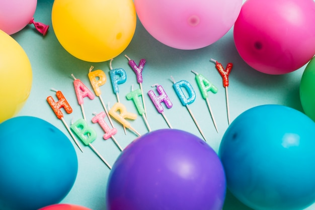 Happy birthday candles stick surrounded with colorful balloons Free Photo