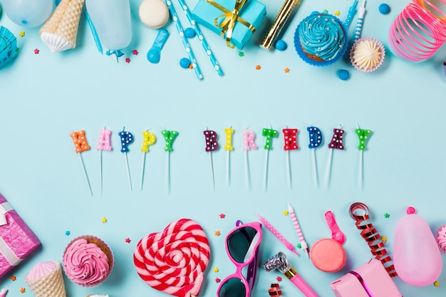 Happy birthday candles with colorful birthday items on blue backdrop Free Photo