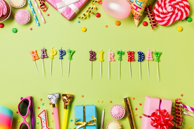 Happy birthday candles with colorful birthday items on green backdrop Free Photo