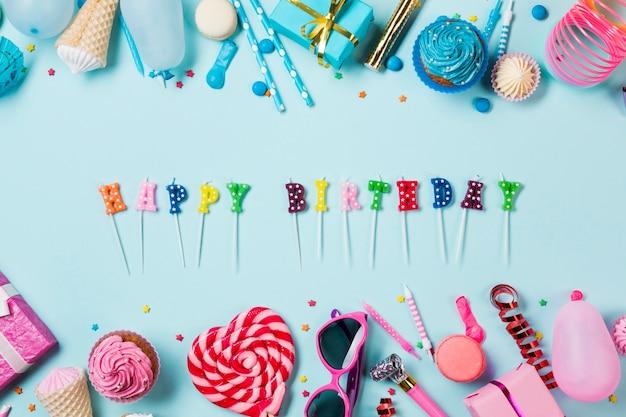 青い背景にカラフルな誕生日アイテムとハッピーバースデーキャンドル 無料写真