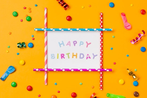 Happy birthday decoration with streamer; balloon; gems and sprinkles on yellow backdrop Free Photo