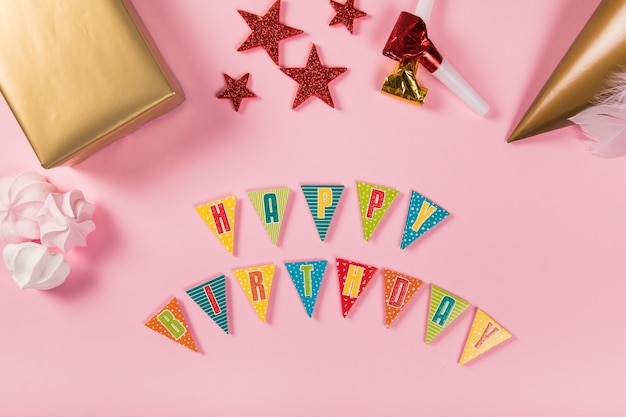 Happy birthday letter with party items and zephyrs on pink background Free Photo