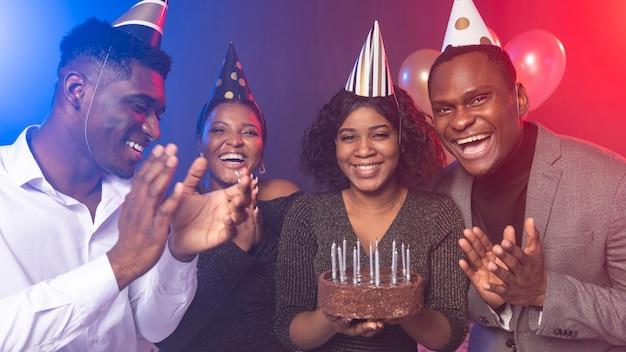 ケーキと友達とお誕生日おめでとうパーティーの女の子 Premium写真