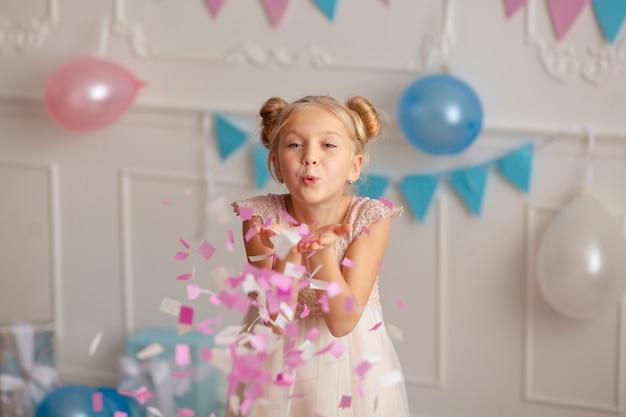 お誕生日おめでとう紙吹雪とギフトでお祝いの装飾が施された7歳から8歳のかわいい金髪の肖像画。 Premium写真