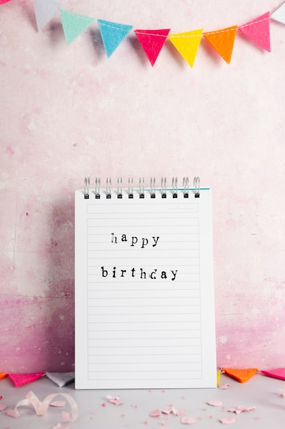 Happy birthday with on notebook with garland Free Photo