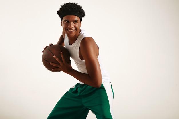 Giocatore di pallacanestro nero felice in vestito verde e bianco che tiene un basket marrone vintage, posa dinamica su bianco Foto Gratuite