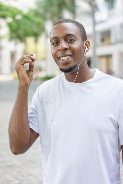 Happy black guy in white tshirt walking outdoors with earphones and enjoying music. Free Photo