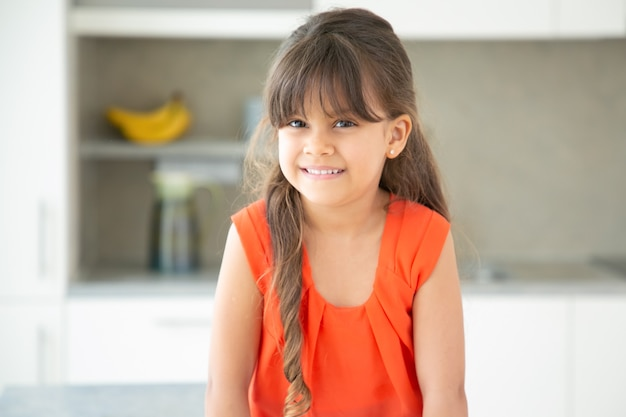 Счастливая черноволосая латинская маленькая девочка в красной футболке позирует дома Бесплатные Фотографии