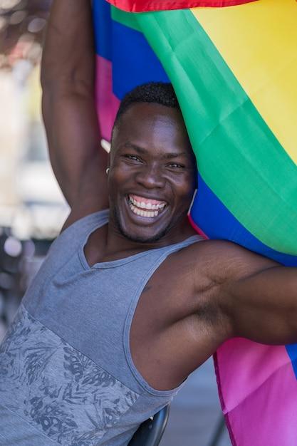 Happy black man with glitter beard holding rainbow flag Premium Photo