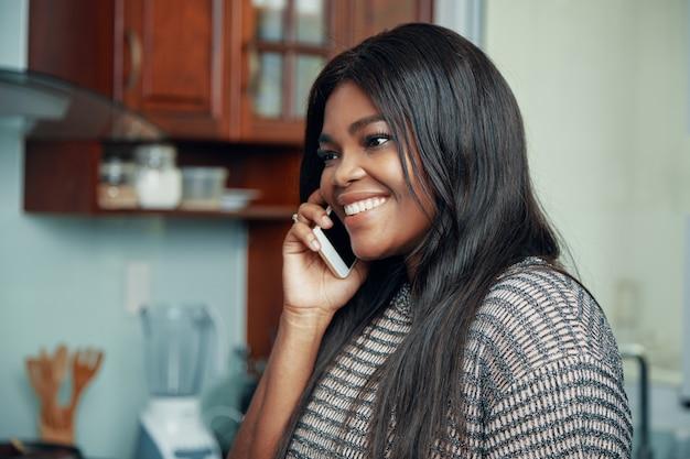 Happy black woman having phone call at home Free Photo