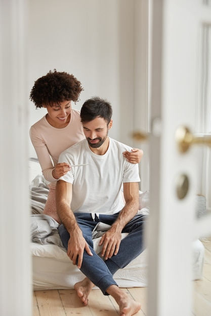 Счастливая темнокожая женщина показывает мужу тест на беременность, довольная положительным результатом, позирует в спальне современной квартиры, радуется хорошим новостям, готова стать родителями. семейная пара в помещении. отцовство Бесплатные Фотографии