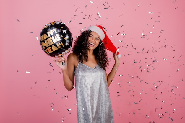 Happy black woman with happy new year balloon and confetti flying in the air isolated over pink Premium Photo