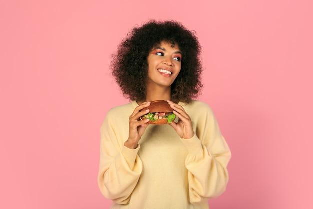 Felice donna nera con i capelli ondulati mangiare gustosi cheeseburger sul rosa. Foto Gratuite