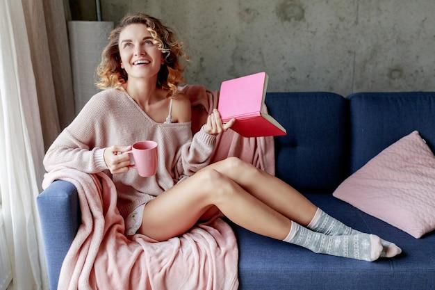 Felice beata ragazza godendo la mattina di sole a casa, tenendo il libro preferito, bevendo caffè. atmosfera calda e accogliente. colori tenui rosa. Foto Gratuite