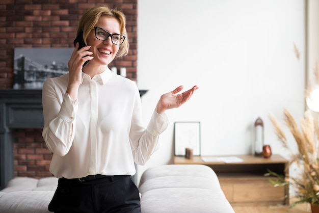 Happy blond business woman talking on phone Free Photo
