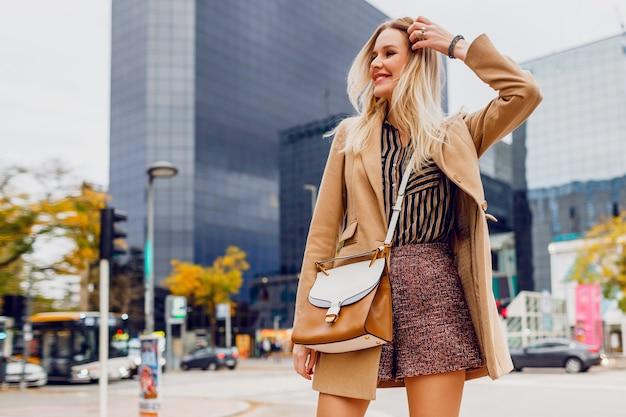 屋外を歩いて、大きな近代的な都市で休日を楽しんでいる春のカジュアルな服装で幸せなブロンドの女の子。ウールベージュのコートと剥奪されたブラウスを着ています。スタイリッシュなアクセサリー。 無料写真
