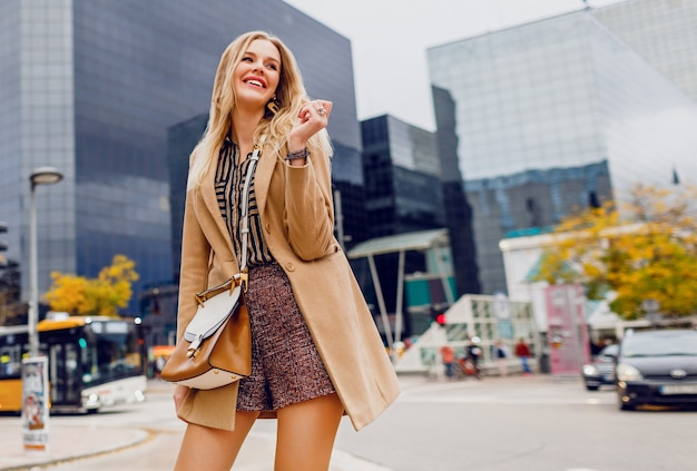 Happy blond woman in spring casual outfit walking outdoor and enjoying holidays in big modern city. wearing wool beige coat, and stripped blouse. stylish accessories. Free Photo