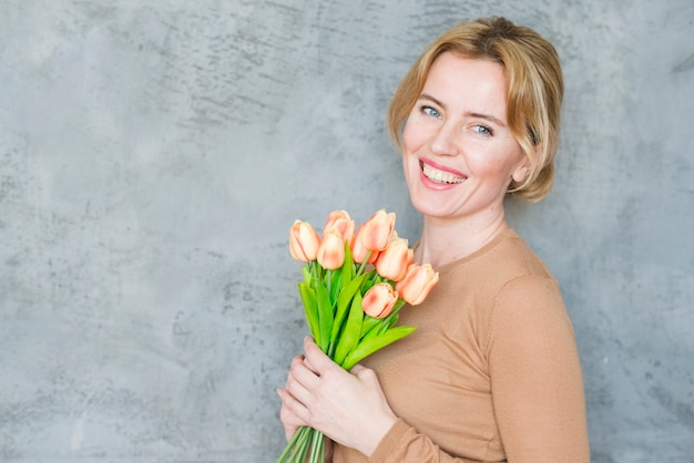 Happy blond woman standing with tulips bouquet Free Photo