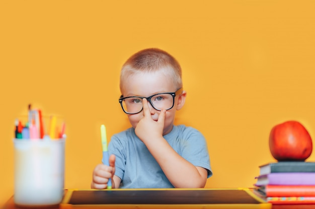Happy blonde clever boy is sitting at a desk in glasses and smiling Premium Photo