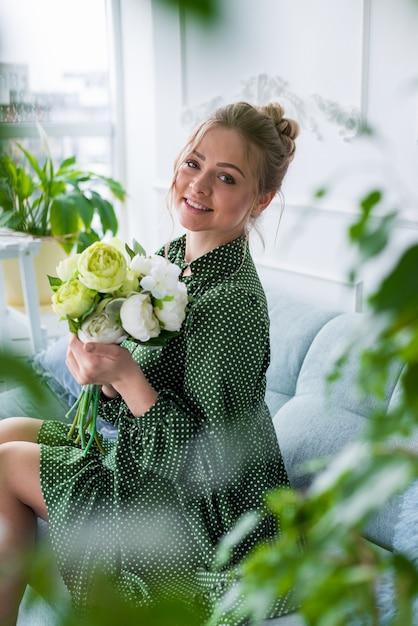 Happy blonde girl in green dress sits on the half-turn holding a bouquet of peonies and looking at  the camera. Premium Photo