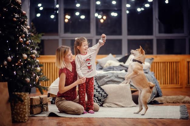 Счастливая светловолосая мать держит свою серьезную дочь в пижаме, сидящую на ковре на полу возле серой кровати, глядя на елку с огнями и подарками перед большими ночными окнами Premium Фотографии