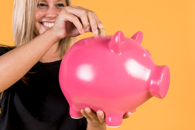 Happy blonde woman inserting coin inside pink piggy bank Free Photo