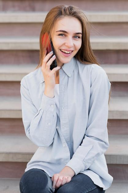 Happy blonde woman talking on phone Free Photo