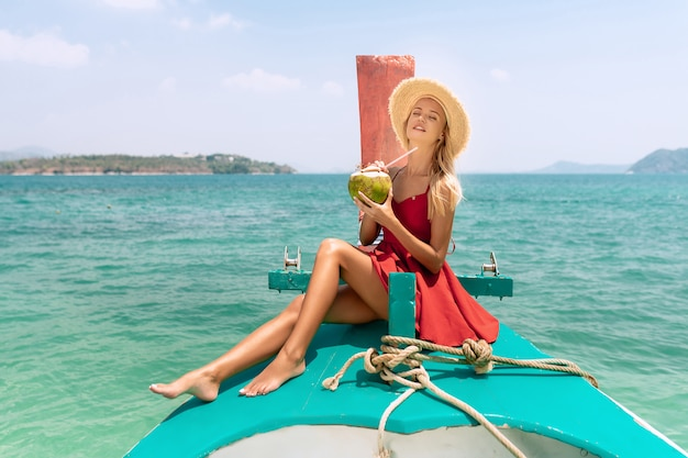 Happy blonde woman traveler in red dress and straw hat relaxing  with coconut on boat Premium Photo