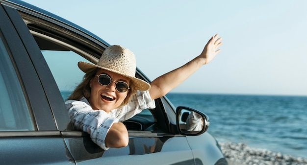 Happy blonde woman with hat looking out of car window Free Photo