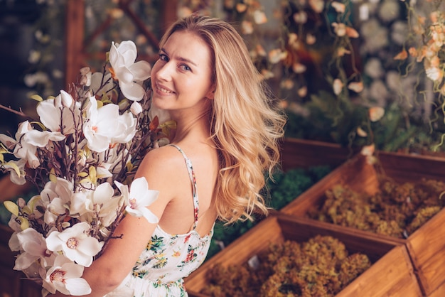 Happy blonde young woman holding camellia bouquet in hand Free Photo