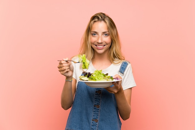 Happy blonde young woman with salad over isolated pink wall Premium Photo