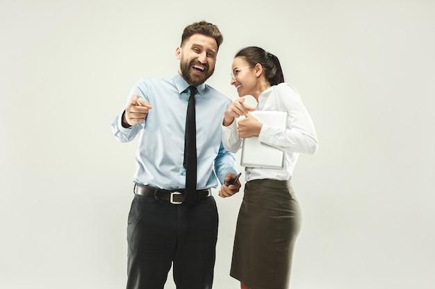 幸せなボス。男と彼の秘書が事務所に立っています。 無料写真